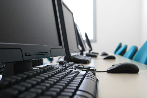 Image of computer monitors with keyboards - Business Insurance